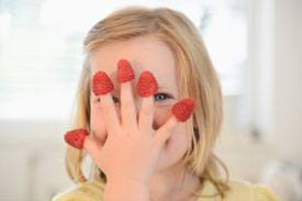 Young girl with five raspberries on her fingers